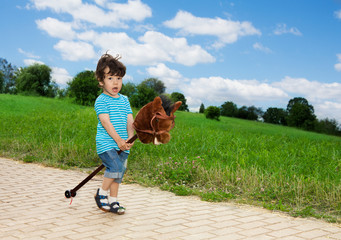 kid playing with horse stick