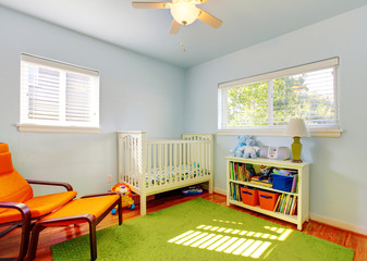 Baby nursery room design with green rug, blue walls