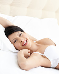 Woman in underwear is lying in the comfortable bed