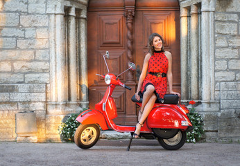 A young woman in a red dress posing near a vintage scooter