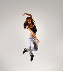 A young and fit female dancer caught in a hilarious jump