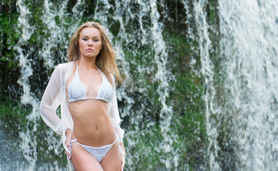 A young blond woman in white lingerie on a waterfall background