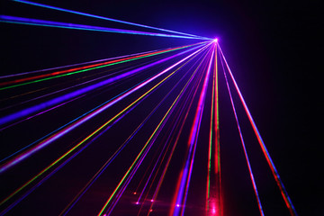 Lot of beautiful multi-colored laser beams in dark at disco.