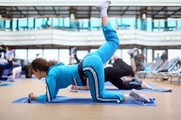 Young woman dressed in tracksuit do exercises in sports hall