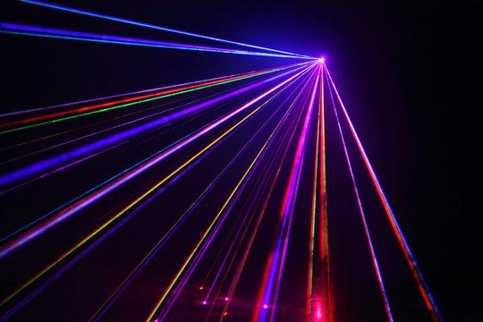 Lot of beautiful multi-colored laser beams in dark at disco.