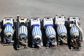 Six concrete mixer machines stand on asphalt at sunny day