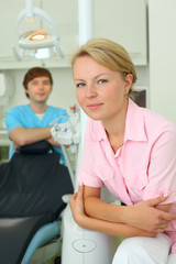 Dentist looks at camera in cabinet of dental clinic
