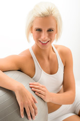 Woman with fitness ball posing on white