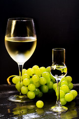 wine and grappa glass with grapes bunch