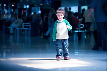 Cute little boy standing at airport