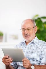 lächelner älterer mann schaut auf sein tablet