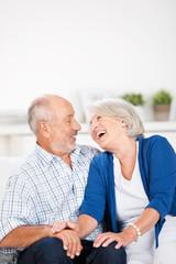 älteres paar sitzt lachend auf dem sofa