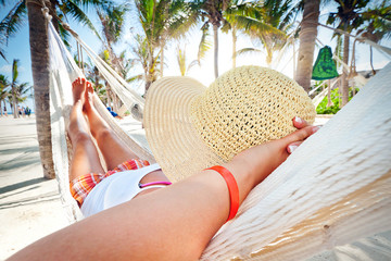 Woman relaxing in the hammock between palm trees