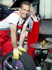 Two motor mechanics fitting a summer tyre in a garage