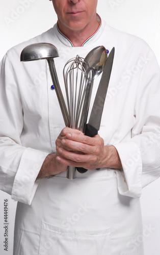 Cocinero chef sujetando utensilios de cocina cocinando for Utensilios para cocineros
