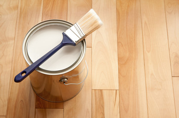 Obraz Paintbrush and a can of white paint on wooden floor - fototapety do salonu