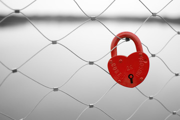 Love padlock on a bridge fence. Russian proverb on it.