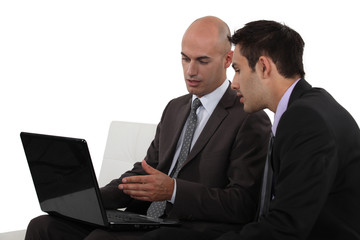 Two businessmen using laptop