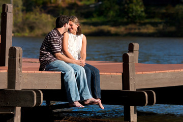 Young Couple Share Intimate Moment Sitting Barefoot On Lake Dock