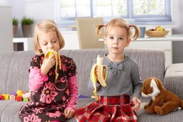 Little sisters eating banana at home
