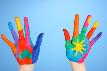 Brightly colored hands on blue background close-up