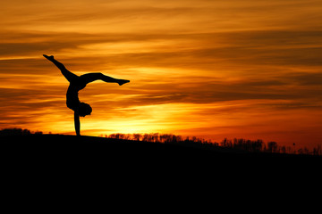 Wall Mural - sunset handstand of female gymnast
