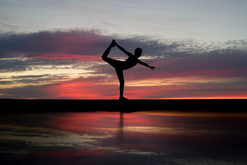 Wall Mural - silhouette of gymnast on beach in after sunset