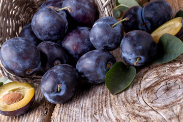 plums scattered on wooden background