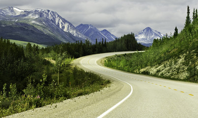 Asphalt road in high mountains of Alaska