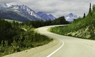 Asphalt road in high mountains of Alaska