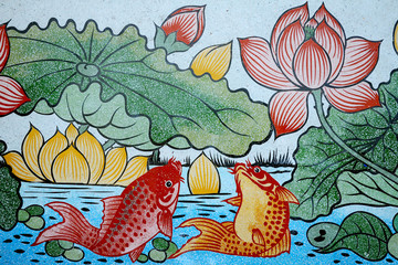 Fishes of Wealth and Lotus painting on stone wall.
