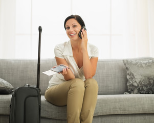 Smiling young woman with passport and air ticket speaking mobile