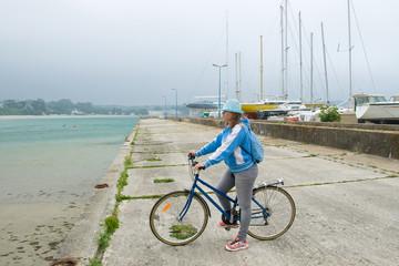 Cyclist girl on the pier.
