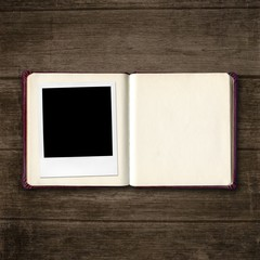 open diary book with photo frame on old wooden table