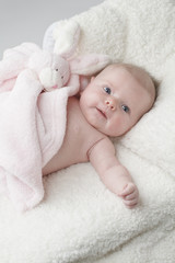 Cute baby with pink toy bunny blanket