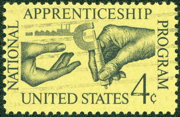 stamp shows the Machinist Handing Micrometer to Apprentice