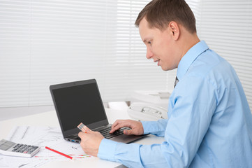 businessman paying online with his credit card at office
