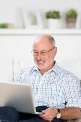 älterer mann arbeitet zuhause am laptop
