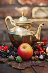 dekorativ arrangierte Herbstfrüchte mit silberner Teekanne
