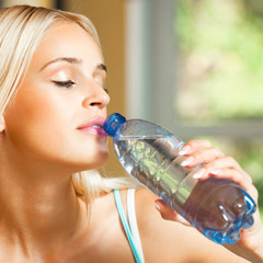 Young beautiful blond woman drinking water