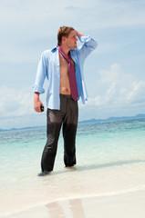 Tired businessman on the beach