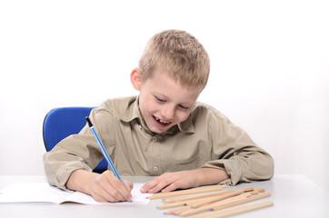 mały chłopiec rysujący kredkami