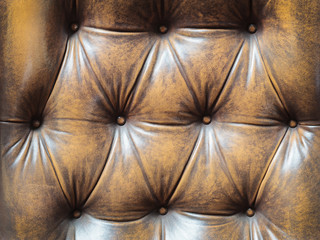 Detail of an old brown couch with buttons