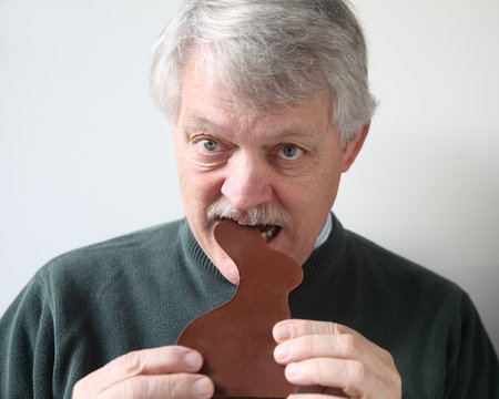 senior man bites into chocolate Easter rabbit