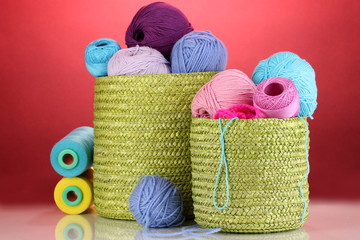 Colorful yarn for knitting in green basket on red background