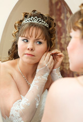 Beauty young Caucasian bride with curly hair looking in mirror and wearing earrings