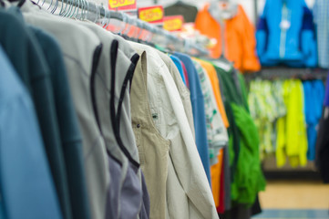 Variety of shirts, vests and t-sirts on stands in supermarket