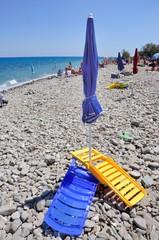 Ombrellone e spiaggine su spiaggia di ciotoli