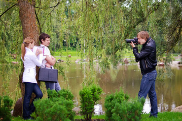 Photographer takes picture of young couple outdoors