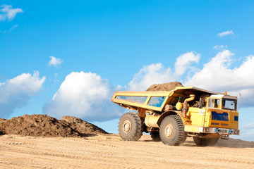 Heavy dump truck unloads soil on the sand at a construction site